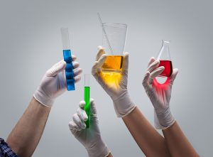 Chemist hands in latex gloves holding laboratory glassware with liquids on light grey background